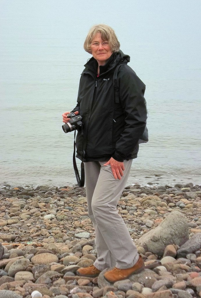 Woman on pebble beach with camera