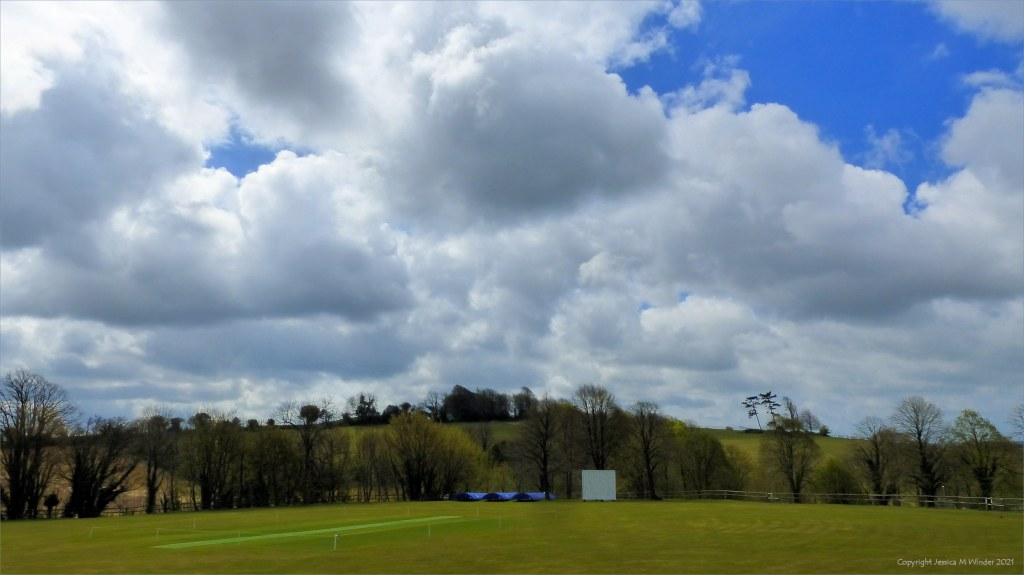 Cricket ground in landscape with cloudy skies