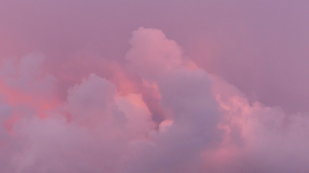 Evening storm clouds reflecting pink light from the setting sun.