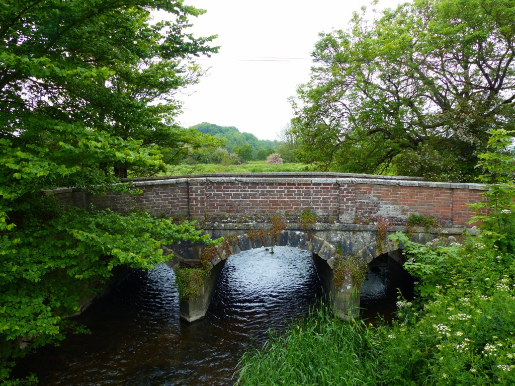 Ancient stone and brick bridge over a river among fields and trees